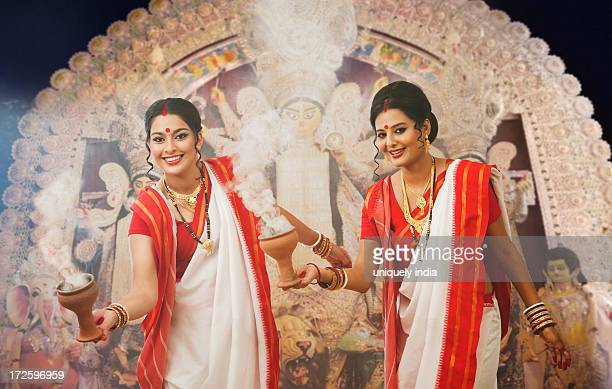 bengali women performing dhunachi dance at durga puja - durga stock photos and pictures