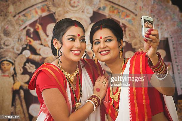 Bengali women taking a picture of themselves with a mobile phone at Durga Puja