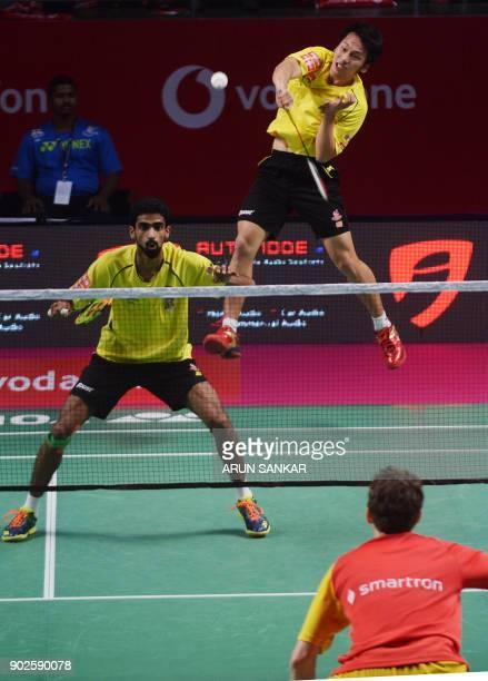 Bengaluru Blasters players Mathias Boe Kim Sa Rang return a shot to Chennai Smashers players Lee Yang and Sumeeth Reddy during their men's badminton...