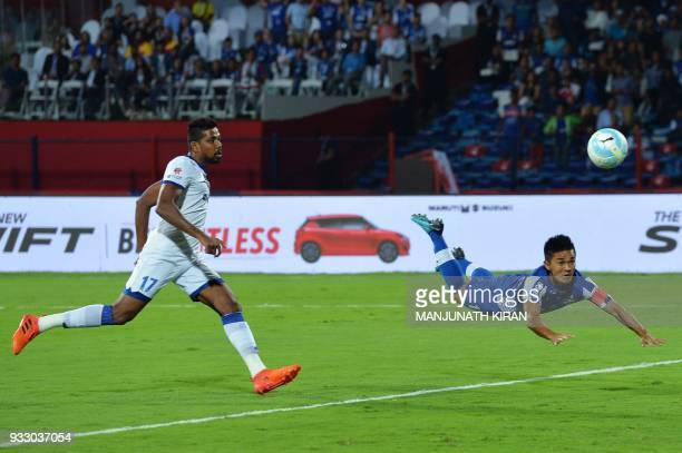 Bengaluru FC captain Sunil Chhetri heads the ball to score a goal as Chennayin FC player Dhanpal Ganesh looks on during the Indian Super League final...