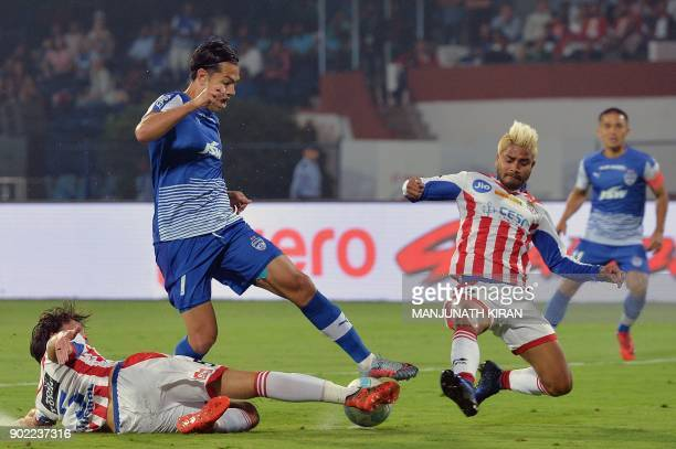 Bengaluru FC player Nicolas Ladislao Fedor vies for the ball with ATK players Thomas Joseph Thorpe and Prabir Das during the Hero ISL football match...