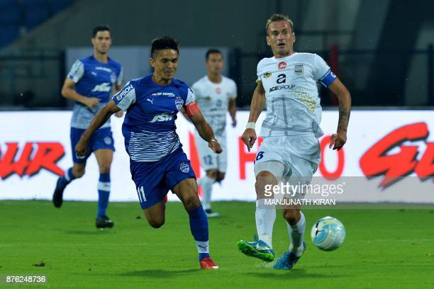 Bengaluru FC player Sunil Chhetri and Mumbai City FC player Lucian Goian compete for the ball during the Indian Super League football match between...