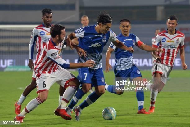 Bengaluru FC players Nicolas Ladislao Fedor and captain Sunil Chhetri vie for the ball with ATK player Jordi Figueras Montel during the Hero ISL...