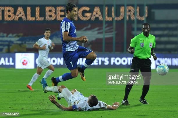 Bengaluru FC's Nicolas Ladislao Fedor jumps over Delhi Dynamos' Guyon Luis Fernandez during the Indian Super League football match between Bengaluru...