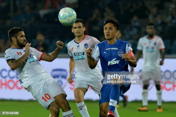 Bengaluru FC's Sunil Chhetri and Delhi Dynamos' Claudio Matias Correa try to head the ball during the Indian Super League football match between...