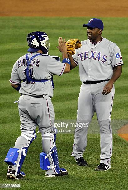 Bengie Molina and Darren Oliver of the Texas Rangers celebrate after they won 103 against the New York Yankees in Game Four of the ALCS during the...