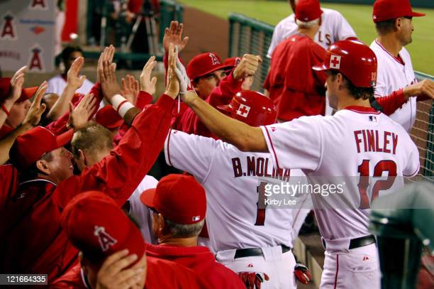 Bengie Molina and Steve Finley of the Los Angeles Angels of Anaheim exchange high fives with teammates after scoring in the sixth inning of 74...