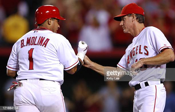 Bengie Molina of the Los Angeles Angels of Anaheim is greeted by thirdbase coach Ron Roenicke after an eighthinning solo home run during 53 victory...