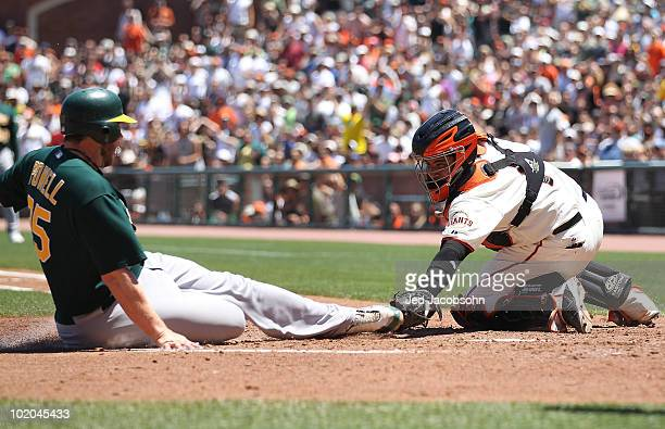 Bengie Molina of the San Francisco Giants tags out Landon Powell of the Oakland Athletics on a single hit by Cliff Pennington in the third inning...
