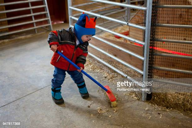 Bengy Hamilton of Brunswick sweeps the barn during the First Time Farmers program at Wolfe's Neck Center in Freeport on Sunday April 15 2018 Bengy...