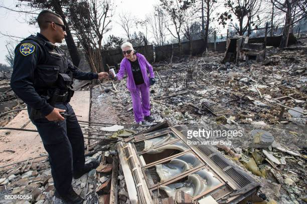 Benicia police officer Alejandro Maravilla left offers resident Gwen Adkins right a soda while patrolling in the Coffey Park neighborhood on October...