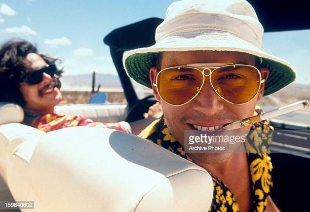 Benicio Del Toro and Johnny Depp in convertible together in a scene from the film 'Fear And Loathing In Las Vegas' 1998