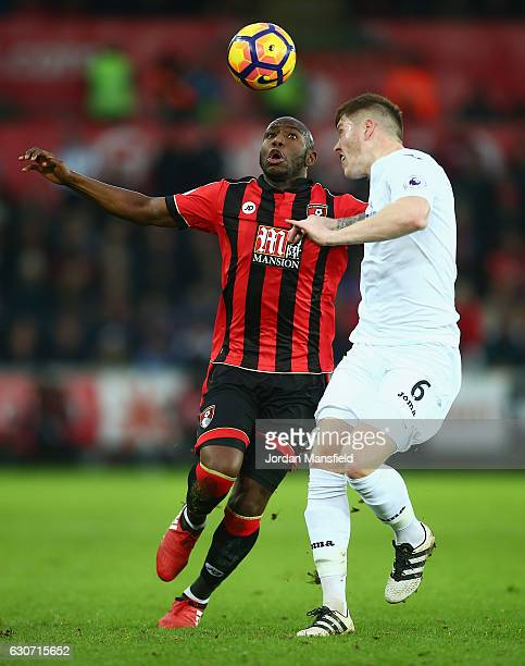 Benik Afobe of AFC Bournemouth and Alfie Mawson of Swansea City head the ball during the Premier League match between Swansea City and AFC...