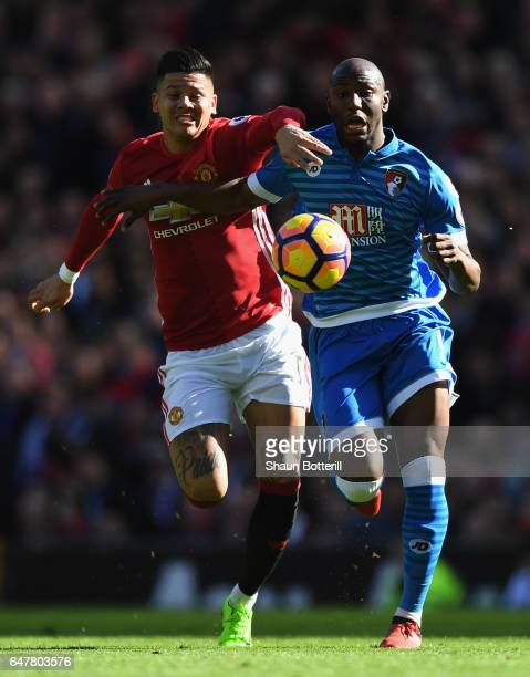 Benik Afobe of AFC Bournemouth is challenged by Marcos Rojo of Manchester United during the Premier League match between Manchester United and AFC...