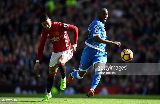 Benik Afobe of AFC Bournemouth slips as he attempts to take the ball past David De Gea of Manchester United while under pressure from Marcos Rojo of...