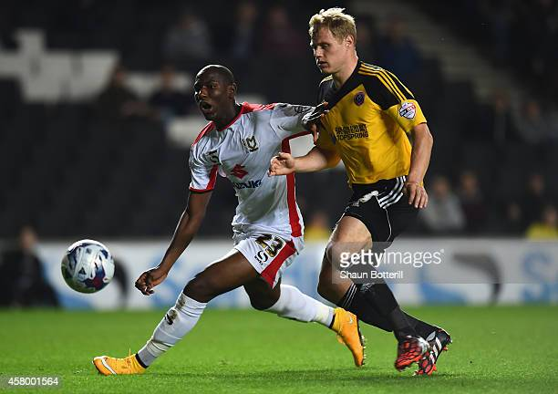 Benik Afobe of MK Dons is tackled by Jay McEveley of Sheffield United during the Capital One Cup Fourth Round match between MK Dons and Sheffield...
