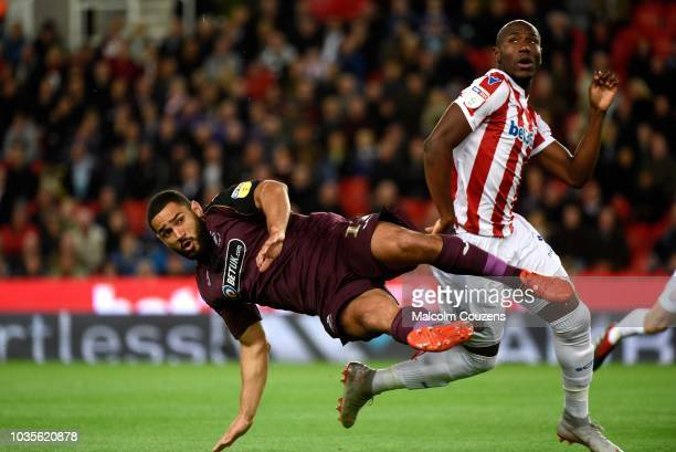 Benik Afobe of Stoke City is challenged by Cameron CarterVickers of Swansea during the game between Stoke City and Swansea City at Bet365 Stadium on...