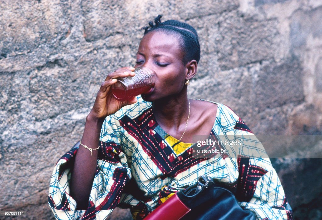 A young woman drinks a tonic mixture of animal blood and herbs to