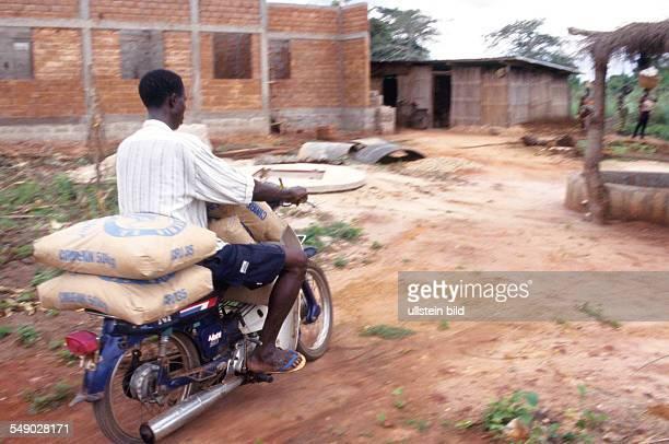 BEN Benin Mono district Adomé A moped cyclist delivering sacks of cement to a construction site of a bush clinic