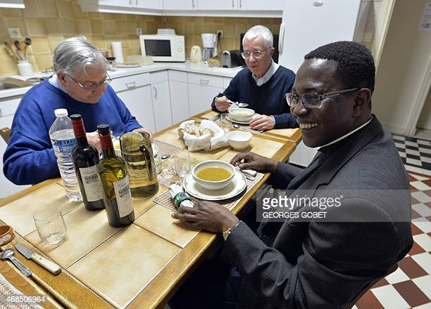 Beninese father Aubin Legodjou and two priests have dinner after the celebration of the Holy Thursday Chrism Mass on April 2 2015 at the church of...