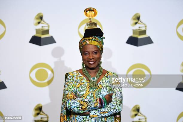 Beninese singersongwriter Angelique Kidjo poses in the press room with the award for Best World Music Album for Celia during the 62nd Annual Grammy...
