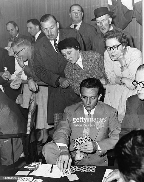 Benito Garozzo plays a tense game of cards in the British Bridge World Challenge Cup as onlookers watch with interest