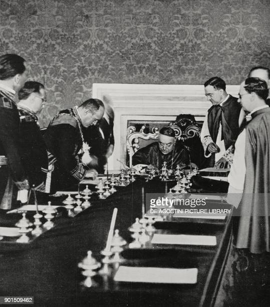 Benito Mussolini and Cardinal Pietro Gasparri signing the ratification of the Lateran Pacts in the Hall of Congregations at the Vatican June 7 from...