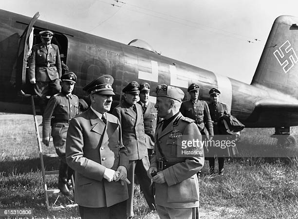 Benito Mussolini and Hitler talk near a German airplane