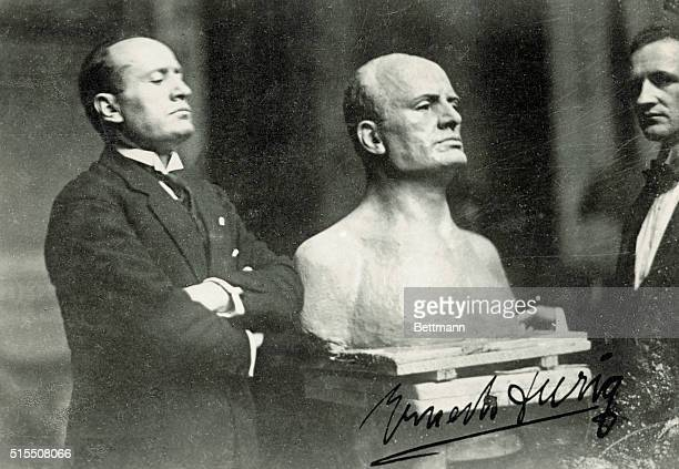 Benito Mussolini , known as IL Duce , Prime Minister and Dictator of Italy, poses beside a bust sculpture of himself. Undated photograph.