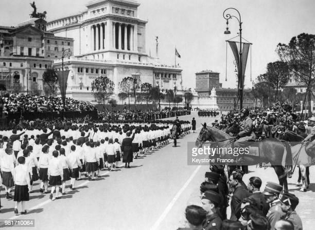 Benito Mussolini passant en revue les jeunes troupes fascistes sur la Via dell'Impero à Rome en Italie lors du 18ème anniversaire de l'entrée en...