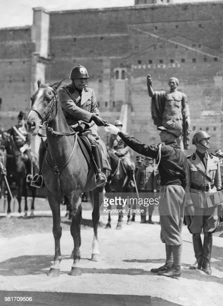 Benito Mussolini récompense un jeune fasciste avanguardisti lors du 18ème anniversaire de l'entrée en guerre de l'Italie à Rome en Italie