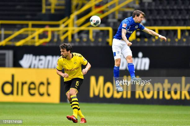 Benito Raman of FC Schalke 04 jumps for the ball with Mats Hummels of Borussia Dortmund during the Bundesliga match between Borussia Dortmund and FC...