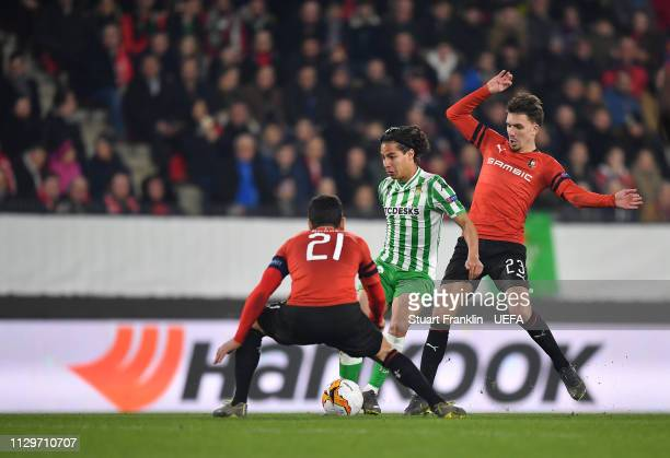 Benjamin Andre and Adrien Hunou of Rennes challenge Diego Lainez of Betis during the UEFA Europa League Round of 32 First Leg match between Stade...