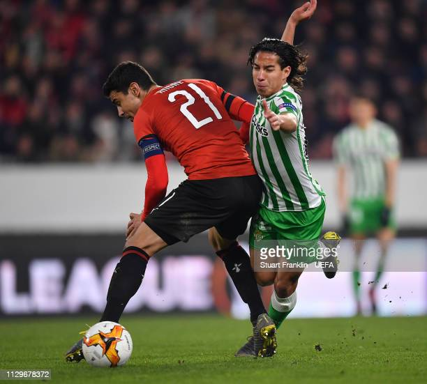 Benjamin Andre of Rennes is challenged by Diego Lainez of Betis during the UEFA Europa League Round of 32 First Leg match between Stade Rennais and...
