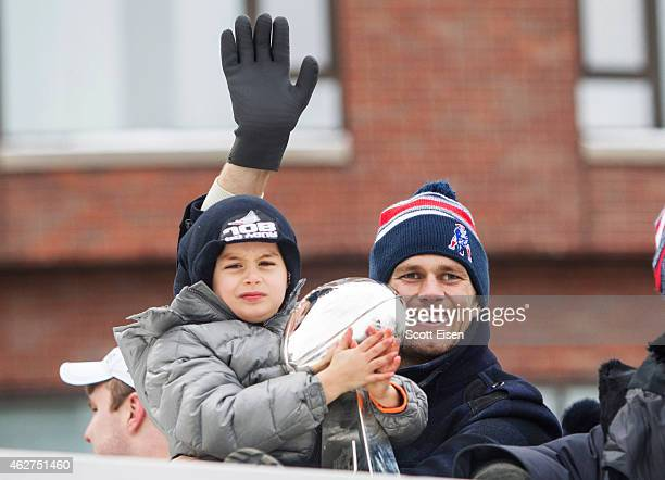 Benjamin Brady holds the Lombardi trophy as his dad Patriots quarterback Tom Brady waves from a duck boat during the New England Patriots victory...