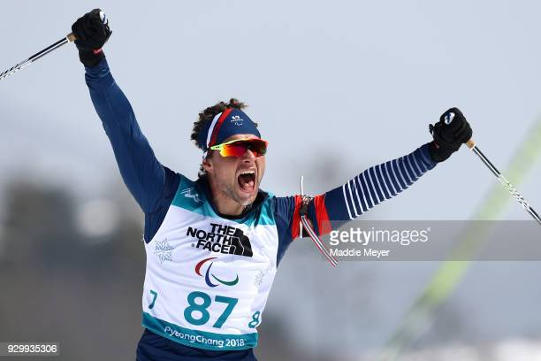 Benjamin Daviet of France celebrates after crossing the finish line during the Mens 75 km Standing Biathlon competition at Alpensia Biathlon Centre...
