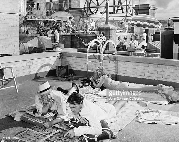 Benjamin Dingle Joe Carter and Connie Milligan sunbathe and socialize on the roof of their apartment house in the 1943 film The More the Merrier
