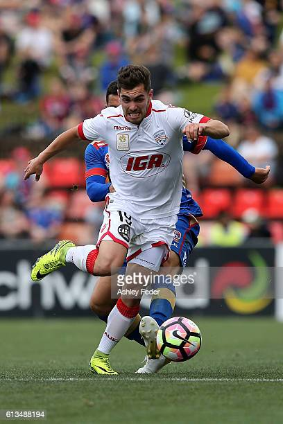 Benjamin Garuccio of Adelaide contests the ball against Andrew Nabbout of the Jets during the round one ALeague match between the Newcastle Jets and...