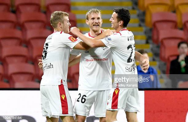 Benjamin Halloran of Adelaide celebrates with team mates after scoring a goal during the round 18 A-League match between the Brisbane Roar and...