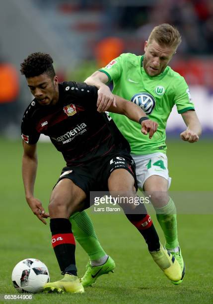 Benjamin Henrichs of Bayer Leverkusen is challenged by Jakub Blaszczykowski of Wolfsburg during the Bundesliga match between Bayer 04 Leverkusen and...