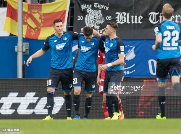 Benjamin Huebner of Hoffenheim celebrates his team's fith goal with team mates Niklas Suele and Ermin Bicakcic during the Bundesliga match between...