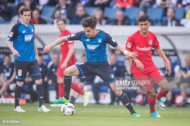 Benjamin Huebner of Hoffenheim is challenged by Aymane Barkok of Frankfurt during the Bundesliga match between TSG 1899 Hoffenheim and Eintracht...