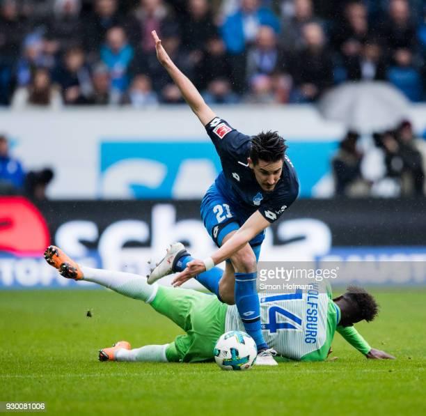 Benjamin Huebner of Hoffenheim is challenged by Divock Origi of Wolfsburg during the Bundesliga match between TSG 1899 Hoffenheim and VfL Wolfsburg...