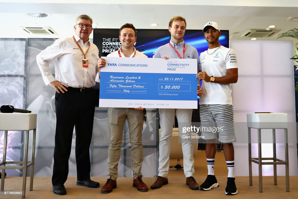 Benjamin Lambert and Alexander Gibson are presented with the Grand Prize by Ross Brawn, Managing Director (Sporting) of the Formula One Group, Lewis Hamilton of Great Britain and Mercedes GP at the F1 Connectivity Innovation prize giving at Yas Marina Circuit on November 23, 2017 in Abu Dhabi, United Arab Emirates.