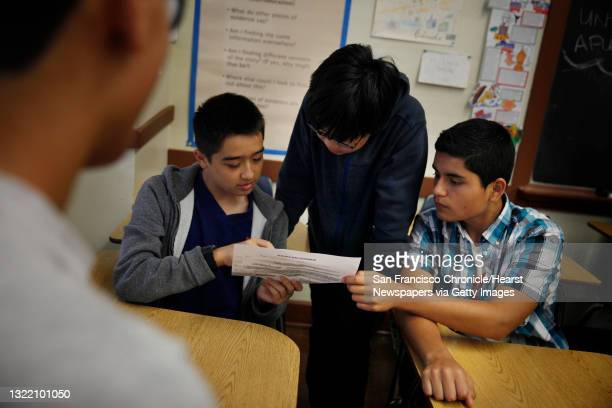 Benjamin Marquarat, 14; Theodore Dong, 14 and Franco Ramirez work together on a classroom exercise brainstorming a topic and research questions...
