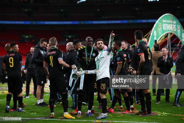Benjamin Mendy and Bernardo Silva of Manchester City hold the trophy with Oleksandr Zinchenko oduring the Carabao Cup Final between Aston Villa and...