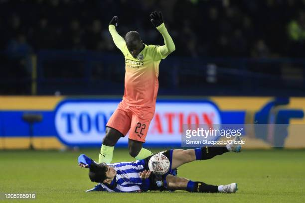 Benjamin Mendy of Man City holds his arms up as Fernando Forestieri of Sheff Wed takes a tumble during the FA Cup Fifth Round match between Sheffield...