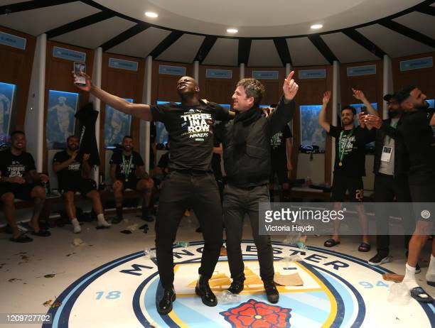 Benjamin Mendy of Manchester City and Noel Gallagher sing in the dressing room following Manchester City's victory in the Carabao Cup Final between...