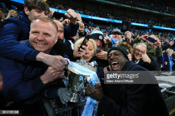 Benjamin Mendy of Manchester City celebrates among the fans with the trophy during the Carabao Cup Final between Arsenal and Manchester City at...