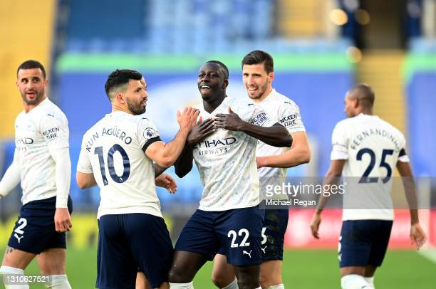 Benjamin Mendy of Manchester City celebrates with team mates Ruben Dias and Sergio Aguero after scoring their side's first goal during the Premier...
